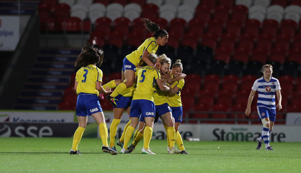 SUBLIME: Emily Simpkins is mobbed by the team after her superb strike vs Reading